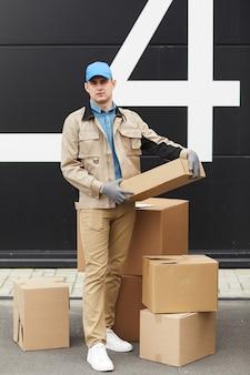 倉庫で小包を操作しながらカメラを見て制服を着た若い宅配便の肖像画