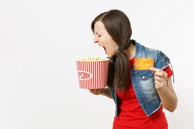 캐주얼 옷을 입고 영화 영화를 보고 팝콘과 신용 카드 양동이를 들고 흰색 배경에 고립 된 비명을 지르는 젊은 미친 갈색 머리 여자의 초상화. 영화 개념의 감정.