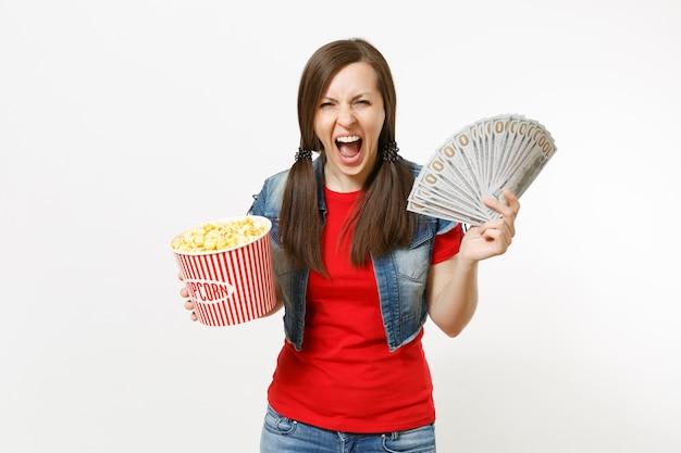 캐주얼 옷을 입고 영화를 보고 팝콘 양동이와 달러 묶음, 현금 돈을 들고 흰색 배경에 격리된 비명을 지르는 젊은 미친 여성의 초상화. 영화 개념의 감정.