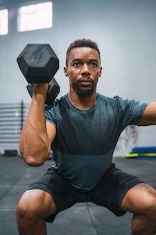 ジムでダンベルで運動をしている若いクロスフィットアスリートの肖像画。 crossfit、スポーツ、健康的なライフスタイルのコンセプト。