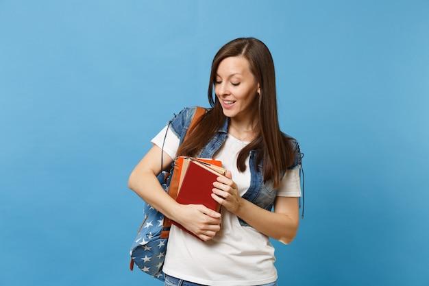 파란 배경에 격리된 학습 준비가 된 책을 들고 책을 내려다보는 호기심 많은 젊은 여성 학생의 초상화. 고등학교 대학 대학 개념의 교육입니다.