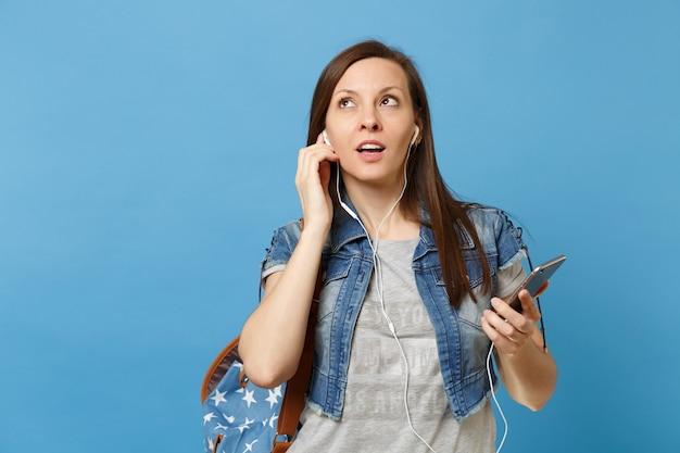 파란색 배경에 격리된 휴대폰을 들고 배낭과 이어폰을 든 호기심 많은 여학생의 초상화. 대학에서 교육입니다. 광고 공간을 복사합니다.