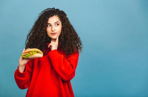 Портрет молодой курчавой красивой голодной женщины, есть гамбургер. изолированный портрет студента с фаст-фудом на синем фоне.