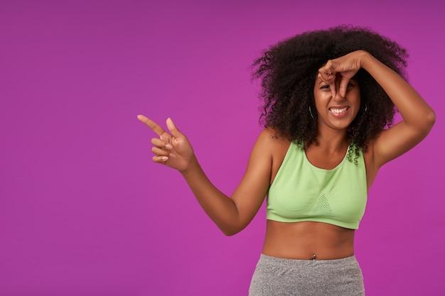 Портрет молодой кудрявой темнокожей девушки со случайной прической, стоящей на фиолетовом и закрывающей нос рукой, избегая неприятного запаха и показывая в сторону указательным пальцем