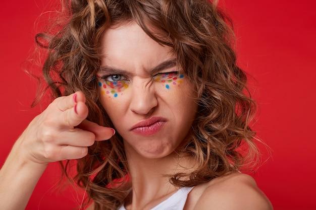 Портрет молодой кудрявой женщины с закрытыми глазами, делает пистолет из руки, выглядит серьезно, щурится и угрожает пистолетом