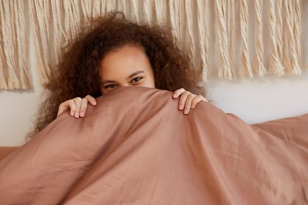 ベッドに横になって笑っている若いかわいいアフリカ系アメリカ人の巻き毛の女性の肖像画は、家で晴れた日を楽しんで、毛布の後ろに円錐形の顔をしています。