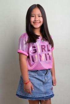 흰 벽에 세련된 옷을 입고 젊은 귀여운 아시아 여자의 초상화