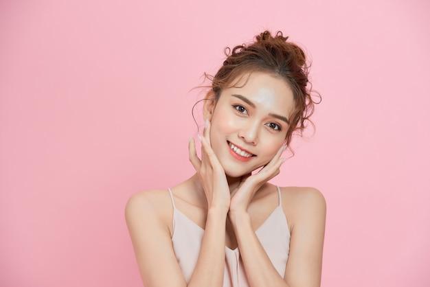 ピンクの背景に笑みを浮かべて若いかわいいアジアの女性の肖像画。