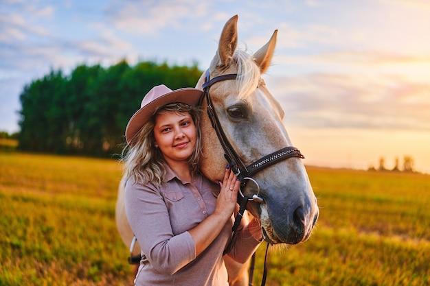 Портрет молодой милой счастливой радостной довольной улыбающейся женщины, обнимающей и поглаживающей красивую белокурую лошадь паломино на лугу на закате