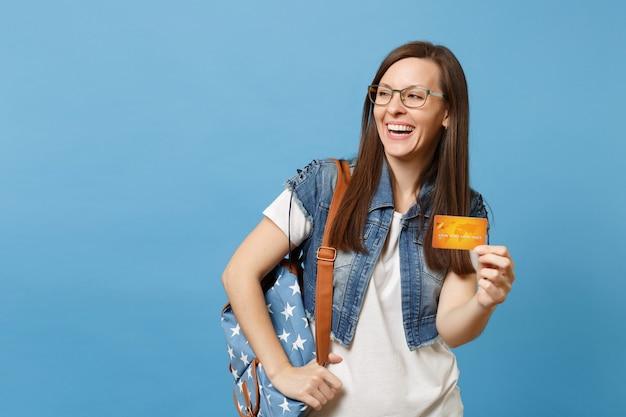 Портрет молодого милого смеющегося студента женщины в стеклах джинсовой одежды при рюкзак смотря в сторону держа кредитную карту изолированную на голубой предпосылке. образование в концепции колледжа университета средней школы.