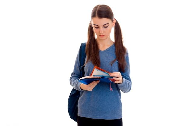 白い背景で隔離のバックパックとノートブックを持つ若いキューティー学生の女の子の肖像画