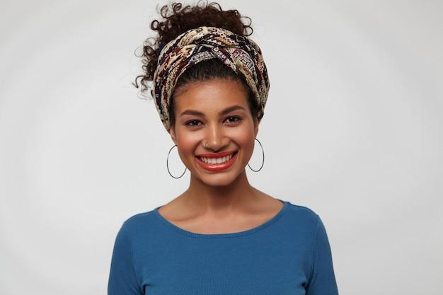 白い背景の上に立って、カメラで元気に笑っている間彼女の白い完璧な歯を示すカジュアルな髪型の若い黒髪の巻き毛のブルネットの女性の肖像画