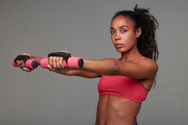 Портрет молодой темнокожей кудрявой брюнетки с прической в розовом спортивном топе, позирующей и делающей упражнения для рук с гантелями