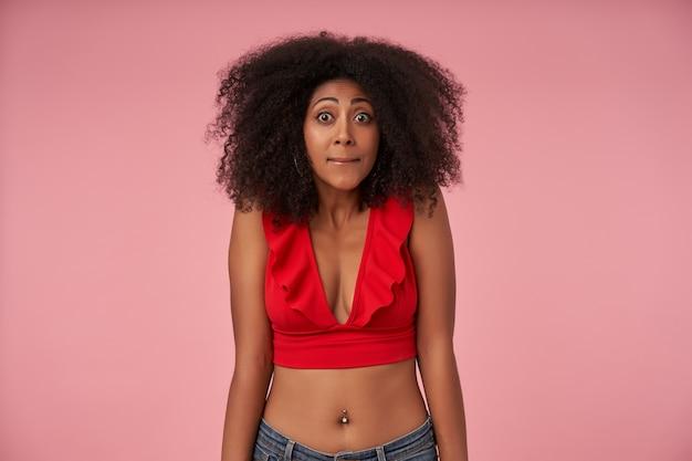 丸い目でカジュアルな髪型、赤いトップとジーンズのピンクの上に立って、眉を上げて唇をすぼめる若い暗い肌の女性の肖像画