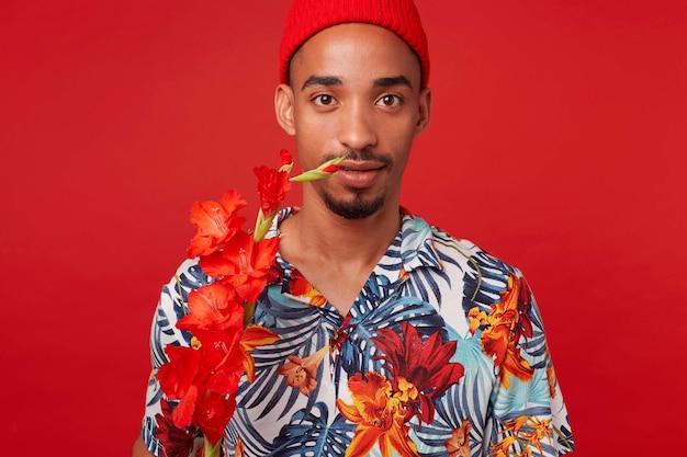 젊은 어두운 피부 남자의 초상화, 하와이안 셔츠와 빨간 모자를 쓰고, 붉은 꽃과 함께 침착 한 표정으로 카메라를 바라보고, 빨간색 배경 위에 선다.