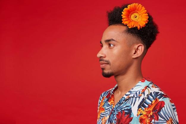 젊은 어두운 피부 남자의 초상화, 하와이안 셔츠를 입고, 머리에 주황색 꽃과 함께 차분한 표정으로 멀리 보이는 빨간색 배경 위에 선다.