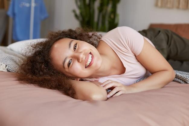 침대에 누워 젊은 어두운 피부 행복 한 여자의 초상화는 광범위 하 게 웃 고, 화창한 아침을 집에서 즐길 수 있습니다.