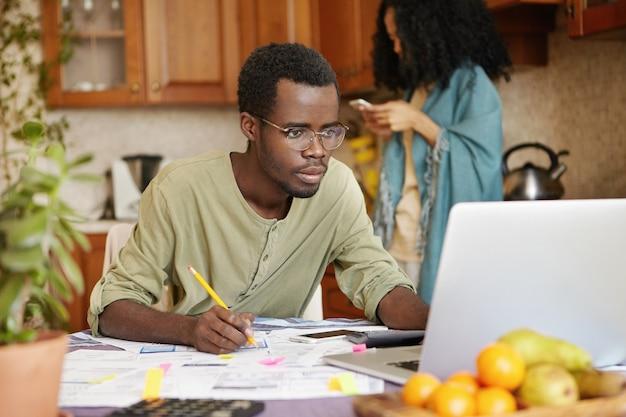 開いているラップトップの前のキッチンのテーブルに座っている眼鏡を身に着けている浅黒い肌の若い男性の肖像画