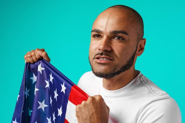 アメリカの国旗を誇らしげに保持している浅黒い肌の若い男の肖像