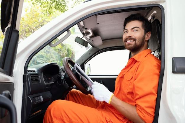 Портрет молодого доставщика готовится завести машину