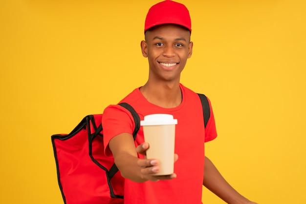 テイクアウトコーヒーのカップを保持している若い配達人の肖像画。配送サービスのコンセプト。