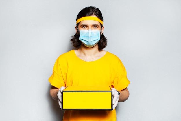 黄色のボックスを保持している若い配達人の肖像画。医療用マスク、サージカルグローブ、オレンジ色のシャツを着用しています。灰色の織り目加工の壁の背景。
