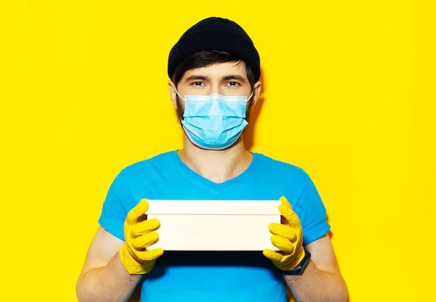 파란색 셔츠에 젊은 배달 남자의 초상화, 의료 얼굴 마스크와 노란색 장갑을 끼고