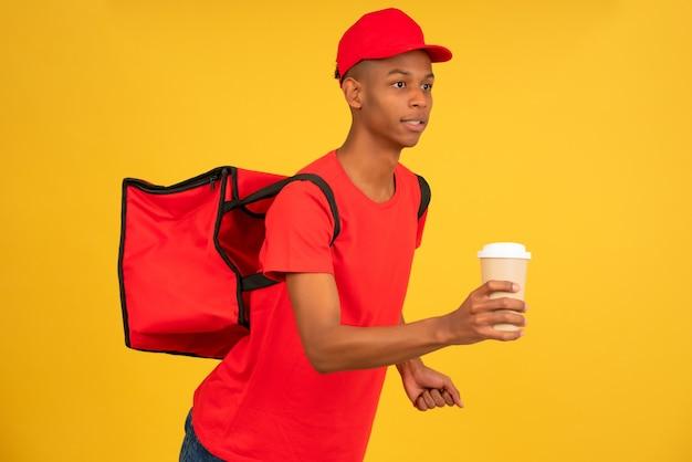 テイクアウトコーヒーと一緒に走っている赤い制服を着た若い配達人の肖像画。配送サービスのコンセプト。