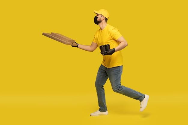 Портрет молодого доставщика в желтой форме с изолированными коробками для пиццы и кофе на вынос