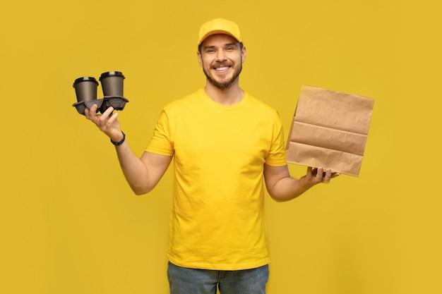 紙のパケットと黄色の壁に隔離された持ち帰り用コーヒーと黄色の制服を着た若い配達人の肖像画