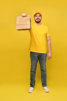 黄色の壁に分離された紙のパケットと黄色の制服を着た若い配達人の肖像画