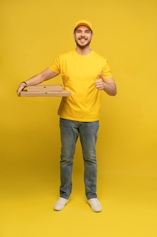 노란색 벽 위에 절연 피자 상자와 노란색 유니폼에 젊은 배달 남자의 초상화