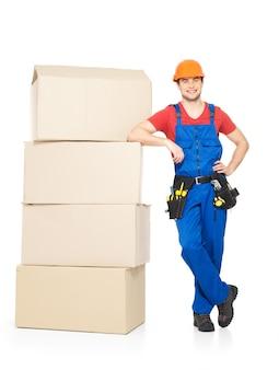 白で隔離の紙箱を持つ若い配達労働者の男の肖像画