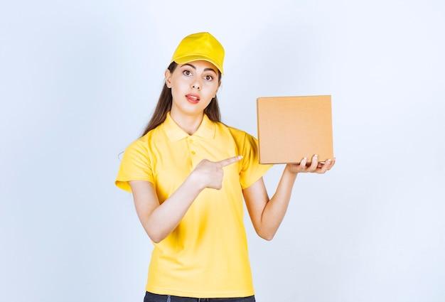 Портрет молодой доставляющей покупки на дом, держа единственную коробку на белом.