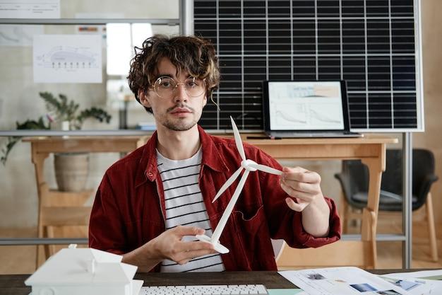Портрет молодого дизайнера, держащего архитектурный макет ветряной мельницы и представляющего его коллегам