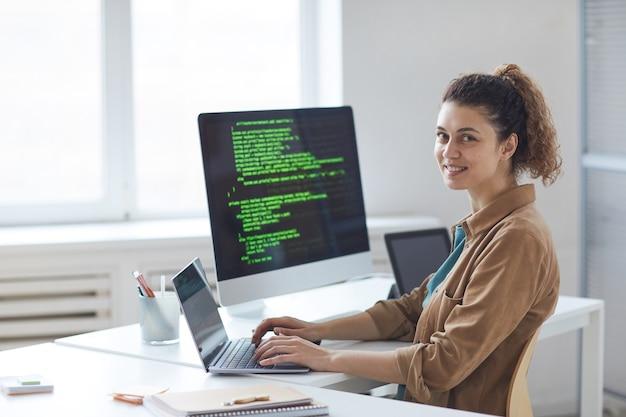Портрет молодого разработчика, улыбающегося спереди, работая над компьютером на своем рабочем месте в офисе