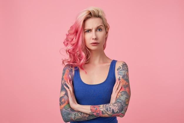 Портрет молодой недовольной красоты женщины с розовыми волосами, хмурится и стоит со скрещенными руками, выглядит грустно, носит синюю рубашку. люди и понятие эмоций.