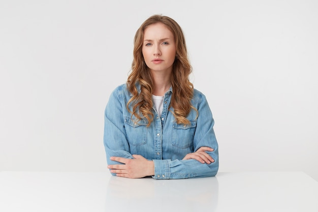 Портрет молодой недовольной блондинки носит джинсовые рубашки, сидя за белым столом, изолированным на белом фоне.