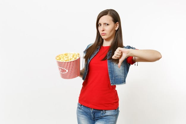 캐주얼 옷을 입고 영화 영화를 보고, 팝콘 양동이를 들고, 흰색 배경에 격리된 엄지손가락을 아래로 보여주는 젊은 불만족스러운 매력적인 브루네트 여성의 초상화. 영화 개념의 감정.
