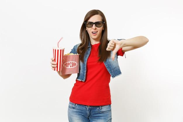 3d 안경을 쓴 불만족스러운 젊은 여성의 초상화가 영화 영화를 보고, 팝콘 양동이와 소다 또는 콜라 플라스틱 컵을 들고 흰색 배경에 격리된 엄지손가락을 아래로 보여줍니다. 영화 속 감정.