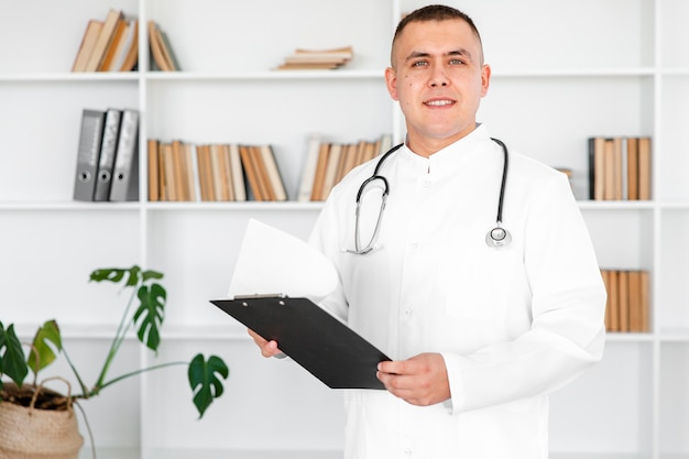 Портрет молодого доктора держа доску сзажимом для бумаги
