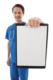 白い背景で隔離の青い制服を着た若い医者の肖像画