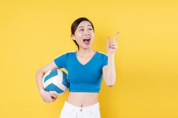 黄色の背景で隔離の手でボールを保持している若いダイナミックな女の子の肖像画