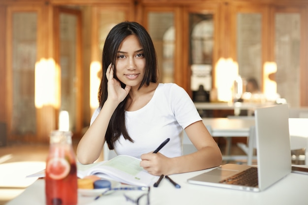 카메라를보고 노트북에서 일하는 레모네이드를 마시는 도서관에서 공부하는 젊은 동부 여자의 초상화.