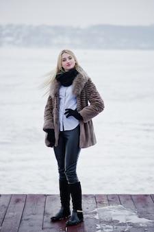 冬の氷の上の霧の川、桟橋で毛皮のコートの若いエレガンスブロンドの女性の肖像画。