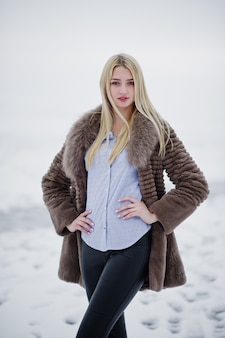 毛皮のコート、冬の氷の霧の川で若いエレガンスブロンドの女性の肖像画。