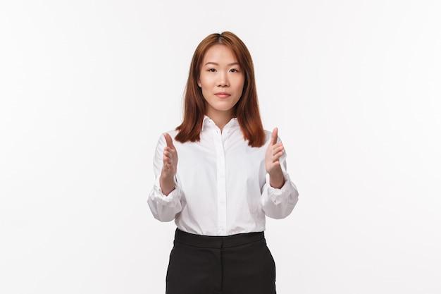 Портрет молодой элегантной азиатской женщины в офисной одежде, указывая на камеру, показывая путь, женщина-инструктор дает указания, обучая новых стюардесс,