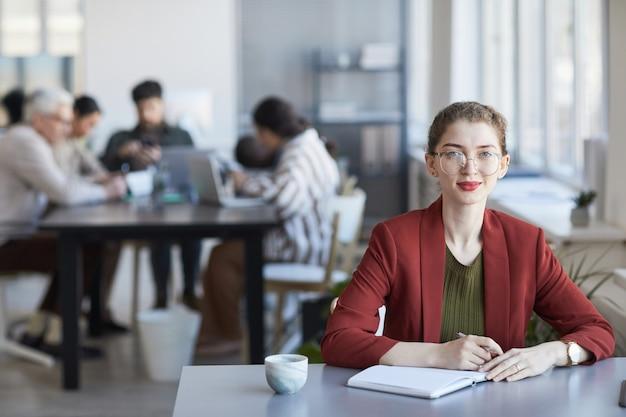 Портрет молодой элегантной бизнес-леди, смотрящей в камеру во время работы за столом в офисе с командой в фоновом режиме, копией пространства