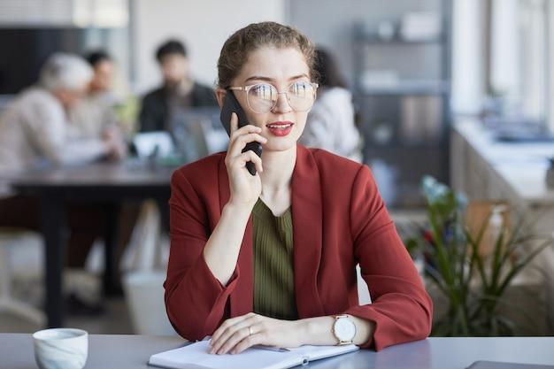 Портрет молодой элегантной бизнес-леди, говорящей по телефону во время работы за столом в офисе с командой в фоновом режиме