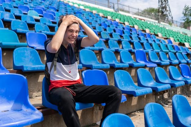 Портрет молодого эмоционального мужчины, сидящего на спортивном стадионе во время матча